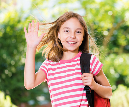 Smiling girl 10-11 year old stretching her right hand up for greeting in summer park. Beautiful schoolgirl with backpack posing outdoors. Stock Photo