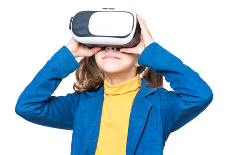 Happy little girl wearing virtual reality goggles watching movies or playing video games. Smiling kid looking in VR glasses. Funny child experiencing 3D gadget technology.