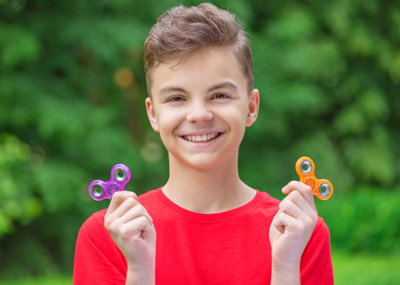 Young teen boy holding popular fidget spinner toy - outdoors portrait. Happy smiling child playing with a orange Spinner in summer park.