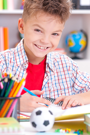 learning by doing: Happy smiling young boy sitting at desk in the classroom or home. Handsome child looking at camera. Stock Photo