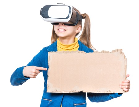 Happy little girl wearing virtual reality goggles watching movies or playing video games. Cheerful smiling kid with VR glasses and corrugated cardboard torn pieces. Funny child experiencing 3D gadget