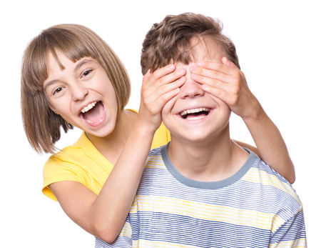 Teen girl covering boys eyes to surprise his. Portrait of brother and sister isolated on white background. Funny couple children laughing with a perfect smile. photo