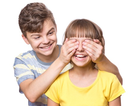 Teen boy covering girls eyes to surprise her. Portrait of brother and sister isolated on white background. Funny couple children laughing with a perfect smile. photo