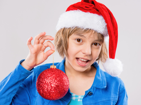 Emotional portrait of attractive caucasian little girl wearing Santa Claus red hat. Funny cute smiling child 10 year old with beautiful Christmas ball on gray background. Winter holiday concept. photo