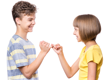 Teen boy and girl on the little finger, hands making promise as a friendship concept. Portrait of happy brother and sister, isolated on white background. photo