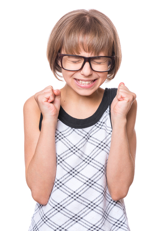 Emotional portrait of attractive caucasian girl, isolated on white background. Schoolgirl celebrating triumph. Child with eyeglasses praying or making luck gesture with eyes closed.