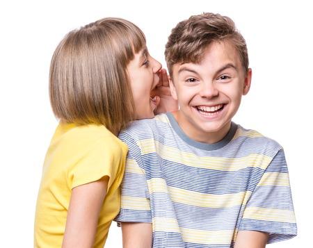 Vriendschap - mooi meisje fluistert iets aan tienerjongen. Portret van gelukkige broer en zus, geïsoleerd op een witte achtergrond. Grappige paarkinderen - eerste liefde. Stockfoto - 84250326