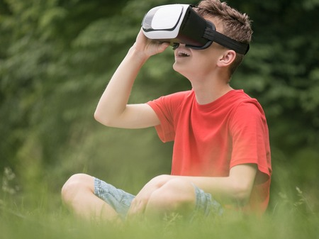Playful teen boy using virtual reality goggles outdoor in summer park. Teenager looking in VR glasses. Child have fun experiencing 3D gadget technology.