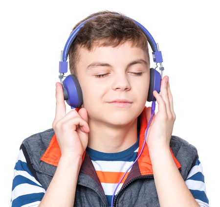 Cheerful handsome teen boy with headphones listening to music, isolated on white background. Emotional portrait of happy cute child 13-15 year old - leisure, children and technology concept.