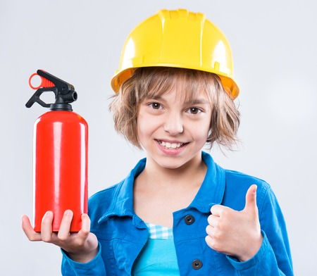 Emotional portrait of attractive caucasian girl wearing safety yellow hard hat. Beautiful happy child holding a fire extinguisher, showing thumb up gesture and looking at camera.
