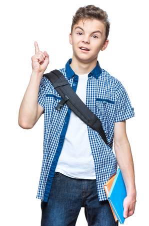 Portrait of cheerful teen boy with good idea. Cute schoolboy with school bag and books pointing up, isolated on white background.