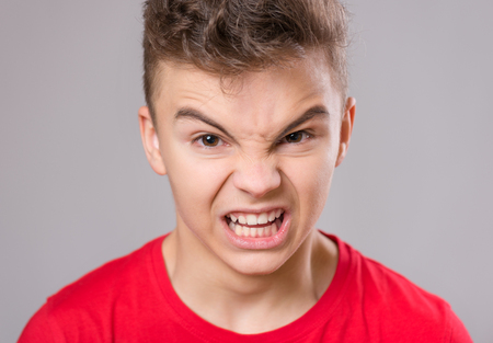 Emotional portrait of irritated shouting teen boy. Furious teenager screaming and looking with anger at camera. Handsome outraged child shouting out loud on gray background.