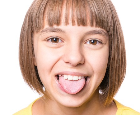 Nice girl showing her tongue. Child puts out tongue - close up. Stockfoto