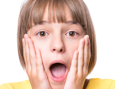 Emotional portrait of excited little girl. Funny cute surprised child 10 year old with mouth open in amazement. Portrait of shocked teenager, isolated on white background.