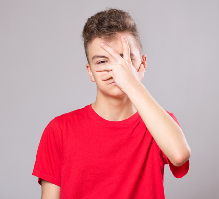 Emotional portrait of caucasian upset problem teen boy. Sad boy looking at camera. Worried  child wearing red t-shirt, on gray background. Stock Photo