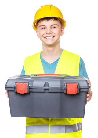 Emotional portrait of handsome teen boy wearing safety jacket and yellow hard hat. Happy child holding toolbox, isolated on white background. Funny cute guy - construction worker or architect.