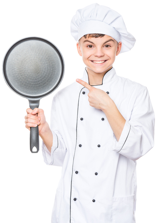 Handsome teen boy wearing chef uniform. Portrait of a happy cute male child cook hiding behind a frying pan, isolated on white background. Food and cooking concept. Stock fotó