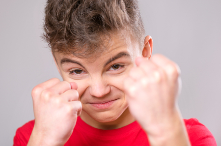 Emotional portrait of irritated teen boy. Furious teenager looking with anger at camera. Handsome outraged child threatens with a fist, isolated on white background.