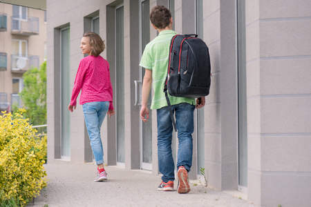 Teen girl and boy 12-14 years old with backpack on the first or last school day. Excited to be back to school after vacation - outdoor back view. Stock Photo