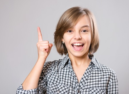 Emotional portrait of excited beautiful girl. Funny cute cheerful child 12 year old. Happy teenager pointing finger up, on gray background.