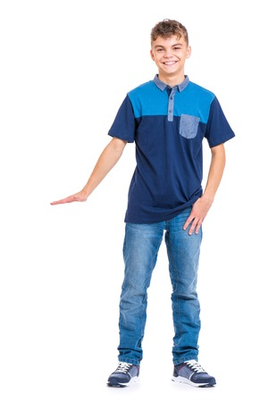 Full length portrait of young caucasian teen boy isolated on white background. Funny teenager showing something by hand. Handsome child looking at camera and smiling.