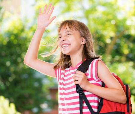 Outdoor portrait of happy child 10-11 years old with backpack. Girl stretching her right hand up for greeting. Back to school concept.