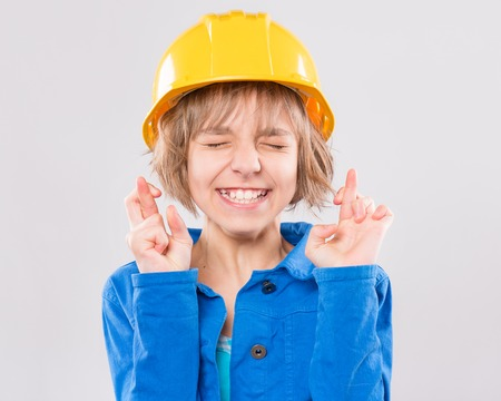 Portrait of attractive girl wearing safety yellow hard hat. Caucasian hopeful girl crossing her fingers. Child - engineer, construction worker or architect making luck gesture, on gray background.
