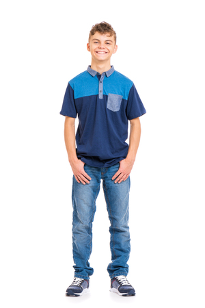 Full length portrait of young caucasian teen boy, isolated on white background. Funny teenager looking at camera and smiling. Handsome child with hands in pockets.