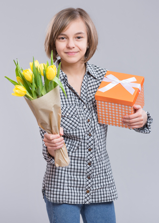 Holidays, love, hapiness and people concept - happy child celebrating Valentines day. Beautiful teen girl with flowers. Funny cute girl with bouquet of yellow tulips on gray background.