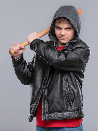 Portrait of a Handsome brutal Teen Boy in a black Leather Jacket with Hood. Displeased Child posing on a gray background. Serious Teenager hooligan holding baseball bat and angrily Looks. Reklamní fotografie - 117171742