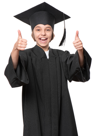 Graduate little happy girl student in black graduation gown with hat making thumbs up gesture - isolated on white background. Child back to school and educational concept.