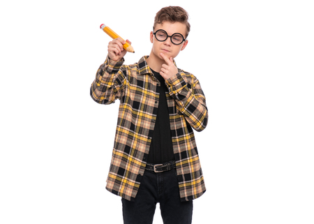 Portrait of Handsome Thoughtful Teen Boy in funny eyeglasses holding Big Pencil. Young Student - ponder and dreaming, isolated on white background. Back to School and childhood concept.