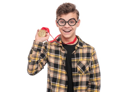 Happy winner. Portrait of Handsome Teen Boy Student in funny eye Glasses holding gold Medal. Child in plaid shirt celebrating his success, isolated on white background. Back to School concept.