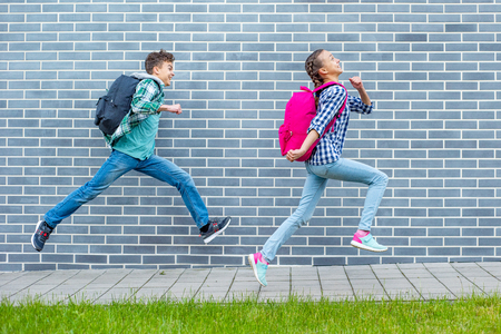 Two happy schoolchildren with backpacks run to school on street next to an Brick Wall. Cheerful cute children pupils Teen Girl and Boy Back to School. Concepts of friends, childhood and education. 免版税图像