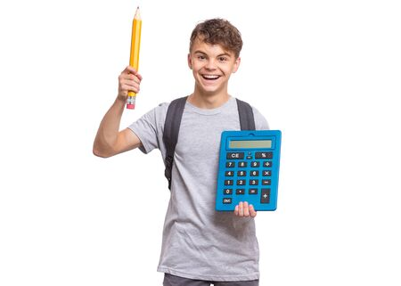 Smart student holding big calculator and pencil. Portrait of funny cute teen boy looking at camera, isolated on white background. Happy smiling child Back to school.