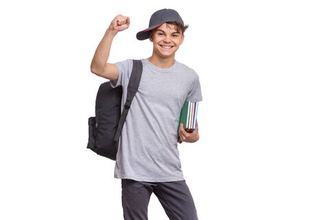 Happy teen boy in cap with books and backpack, isolated on white background. Smiling successful child winner with raised hands, clenching fist, looking at camera. Portrait of teenager Back to school.