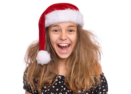 Christmas teen girl in Santa Hat. Cute child in Santa red hat laughing and looking at camera, isolated on white background. Joyful teenager close up portrait. Winter holidays. Happy xmas and New Year
