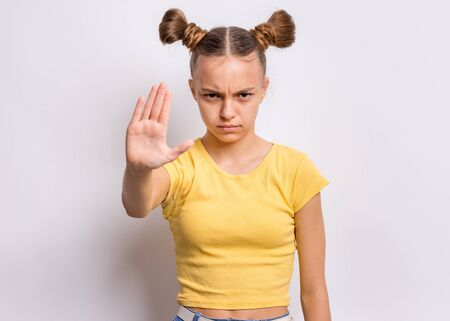 Portrait of teen girl doing stop sing with palm of hand, on gray background. Beautiful caucasian teenager making stop gesture with negative and serious facial expression. Angry child looking at camera
