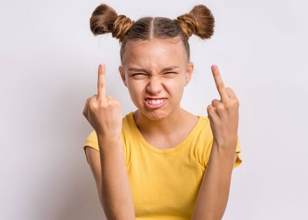 Portrait of angry teen girl showing middle finger, on gray background. Beautiful caucasian young teenager making grimace and obscene gesture. Cute child shows bad sign and looking at camera.