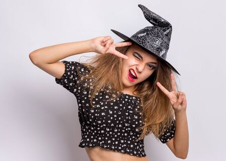 Happy halloween concept. Cheerful Teen girl in witch black hat winking and making Victory Gesture on grey background. Cheering young teenager in witch halloween costume, smiling and looking at camera