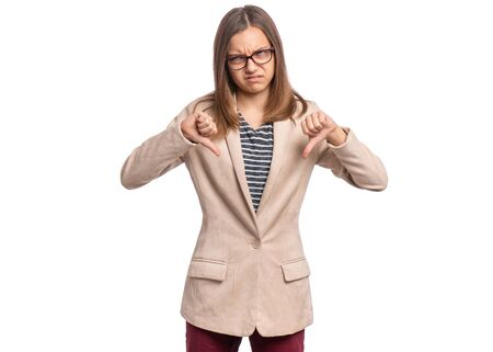 Portrait of teen girl wearing glasses giving thumb down gesture looking with negative expression and disapproval. Beautiful caucasian young teenager doing bad signal, isolated on white background.