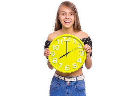 Smiling Teen Girl holding Big Clock, isolated on white background. Portrait of caucasian funny teenager showing big clock. Happy Child back to school. Education and time concept. Stock Photo