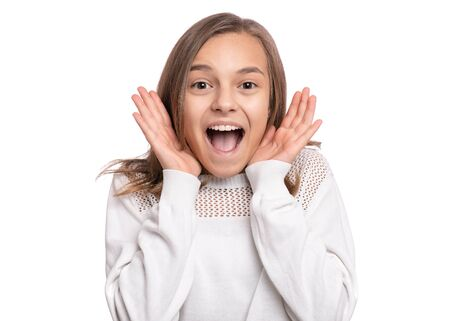 Surprised happy young teen girl, isolated on white background. Funny child looking at camera with mouth open in amazement. Emotional portrait of caucasian teenager.