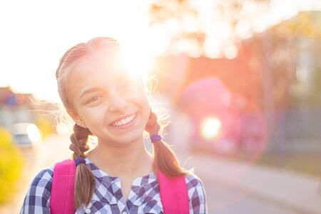 Close up portrait of cheerful teenage girl with backpack in sun rays. Happy smiling teen with bag go to school with fun or returning home in flare sunshine. Child showing tongue