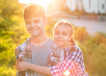 Portrait of Two smiling children against sunset outdoors. Cute teen girl hugs boy in sun rays. Happy family - sister and brother, walking at summer park. Concepts of friends, childhood or first love. Stockfoto