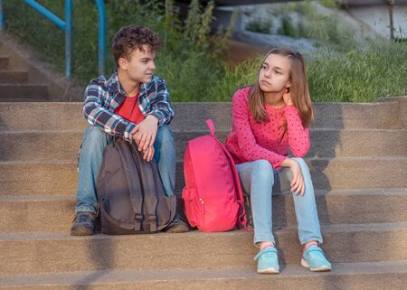 Unhappy teenage boy and girl sitting on stairs outdoors. Sister and brother teens with backpacks. Sad children do not want to go to school. Childhood and Back to school concept.