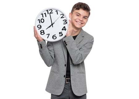 Portrait of caucasian Teen Boy in grey suit with clock. Funny teenager showing big Clock. Child back to school, isolated on white background. Education and time concept.