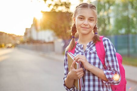 Portrait of teenage girl with backpack and books in sun rays. Happy smiling teen with bag go to school with fun or returning home in flare sunshine. Concepts of Back to School, childhood and education