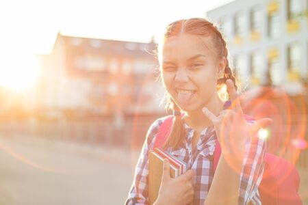 Close up portrait of cheerful teenage girl with backpack in sun rays. Happy smiling teen with braided hair go to school with fun or returning home in flare sunshine. Child showing tongue 版權商用圖片