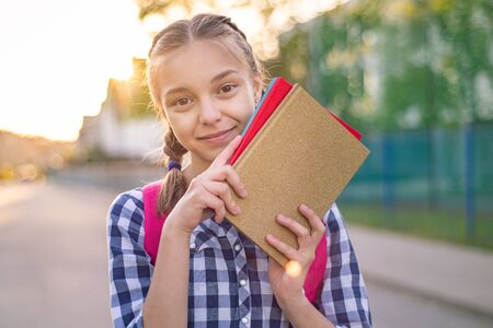 Portrait of teenage girl with backpack and books in sun rays. Happy smiling teen with bag go to school with fun or returning home in flare sunshine. Concepts of Back to School, childhood and education Stockfoto - 128566067
